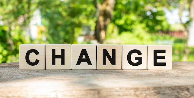 Six wooden blocks lie on a wooden table against the backdrop of a summer garden and create the word change.