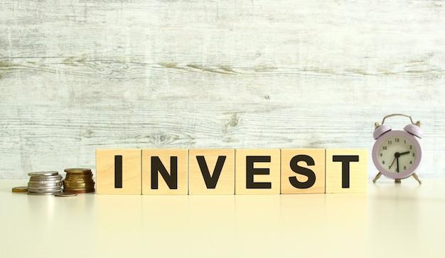 동전 옆 탁자 위에 글자가 있는 6개의 나무 큐브가 있습니다. 단어는 투자입니다. 회색 배경에.