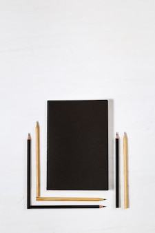 Six wooden pencils and closed black book