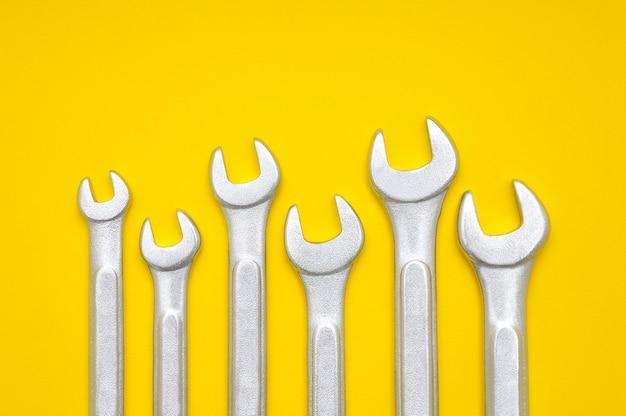 テキストとデザインのためのスペースのある黄色の6つのレンチ