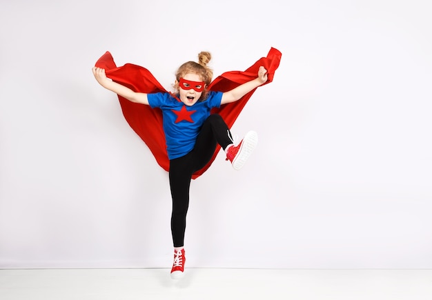 家で楽しんでいるスーパーヒーローのような格好をした6歳のブロンドの女の子。背景の白い壁。