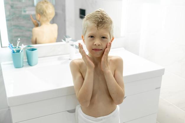 6歳の男の子がお風呂で朝のお父さんのようにアフターシェーブローションを適用し、朝に衛生
