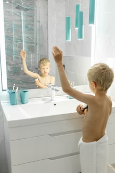 A six-year-old boy shaves his armpits with an electric razor in the bath in front of a mirror, hygiene in the morning