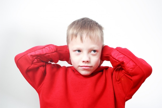 Six-years old boy in red hoodie closing ears with his hands on grey wall. autism concept. protective pose, protectiveness, childhood traumatic experience.