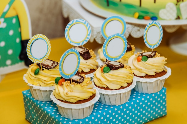 Six yellow cupcakes with pieces of paper for text