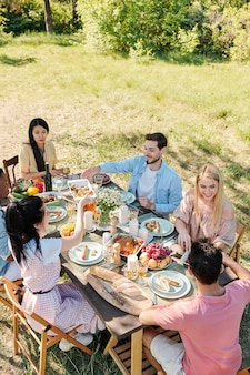 Six young friends of various ethnicities gathered by served table for dinner, they are talking and enjoying homemade food on summer day