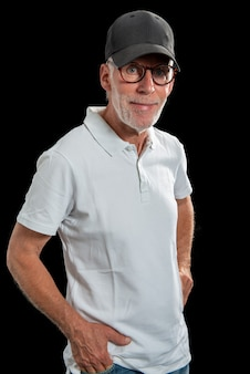 Sixty year old man wearing a baseball cap on black background