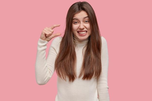 Le misure contano. la giovane donna castana soddisfatta mostra un oggetto molto piccolo, sorride positivamente, indossa un maglione bianco casual