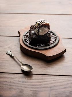 焼けるように暑いチョコレートブラウニーは、溶かしたチョコレートをたっぷりと注いで、上にアイスクリームのスクープを使用して作られた甘い料理です。サーバーが高温になっています。セレクティブフォーカス