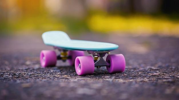 Скейтборд заделывают открытый. пенни доска с розовыми колесами.
