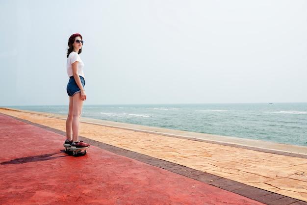 スケートボードレクリエーションの追求の夏のビーチの休日の概念