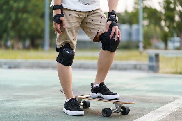スケートボードの安全装備とパッド。街の周りのスケートボードを持つアジア人男性
