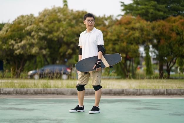 Skateboarder夏の日に街の通りでスケートボードを楽しんでいるアジア人男性。