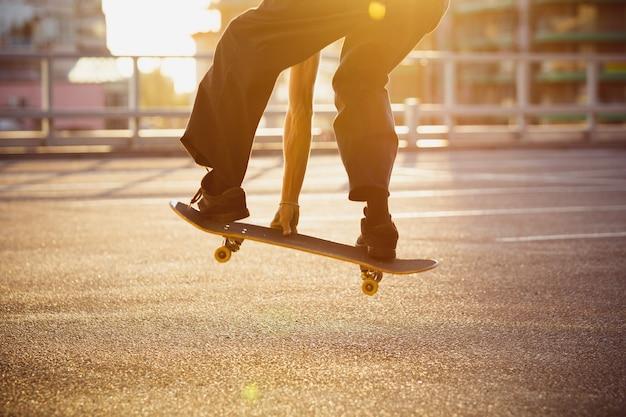 도시의 거리에서 트릭을 하는 스케이트보더, 순간을 닫습니다. 운동화와 모자를 쓰고 아스팔트에서 스케이트보드를 타는 청년. 여가 활동, 스포츠, 익스트림, 취미 및 모션의 개념.