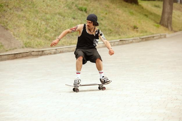 曇りの日に街の通りでトリックをしているスケートボーダー。スニーカーとキャップに乗ってアスファルトでロングボードをしている若い男。余暇活動、スポーツ、エクストリーム、趣味、運動の概念。