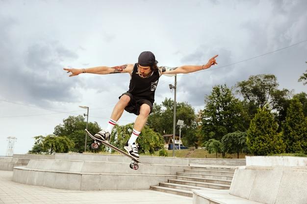 Скейтбордист делает трюк на улице города в пасмурный день