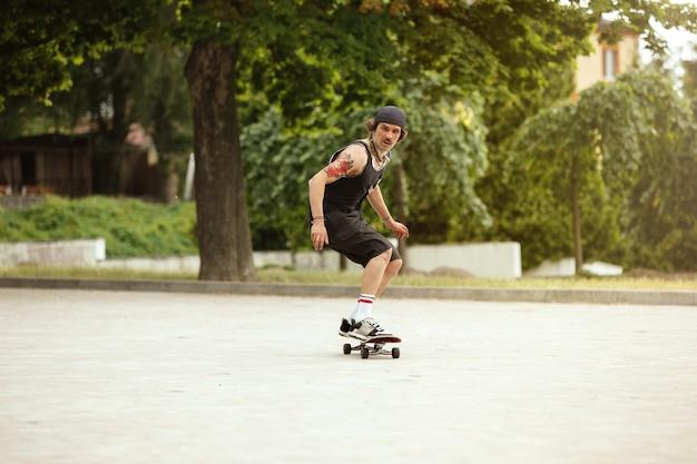 曇りの日に街の通りでトリックをしているスケートボーダー