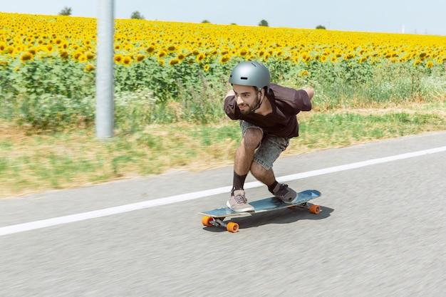 晴れた日に街の通りでトリックをしているスケートボーダー。装備に乗ってロングボードをしている青年。余暇活動、スポーツ、エクストリーム、趣味、運動の概念。車と同じくらい速い。