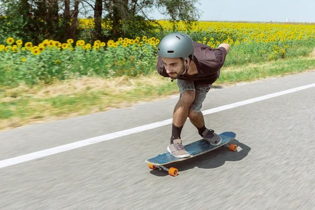 晴れた日に街の通りでトリックをしているスケートボーダー。装備に乗ってロングボーディングをしている青年。余暇活動、スポーツ、エクストリーム、趣味、運動の概念。車と同じくらい速い。
