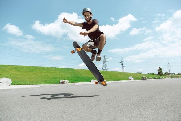 晴れた日に街の通りでトリックをしているスケートボーダー。動作中の牧草地の近くで機器に乗ってロングボードをしている若い男。余暇活動、スポーツ、エクストリーム、趣味、運動の概念。