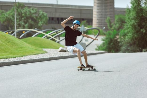 Скейтбордист делает трюк на улице города в солнечный день. молодой человек в снаряжении верховой езды и лонгбординга на асфальте в действии. концепция досуга, спорта, экстрима, хобби и движения.