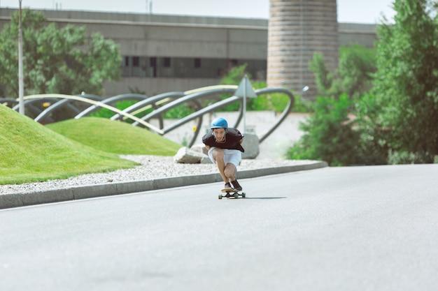 晴れた日に街の通りでトリックをしているスケートボーダー。動作中のアスファルトに乗ってロングボードをしている機器の若い男。余暇活動、スポーツ、エクストリーム、趣味、運動の概念。