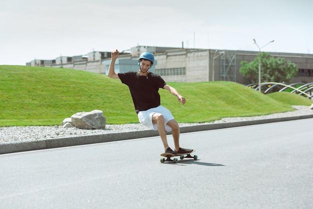 화창한 날에 도시의 거리에서 트릭을하는 스케이트 보더