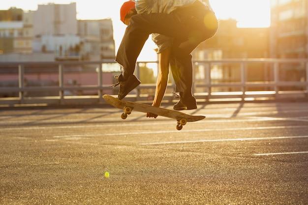 夏の日差しの中で街の通りでトリックをしているスケートボーダー