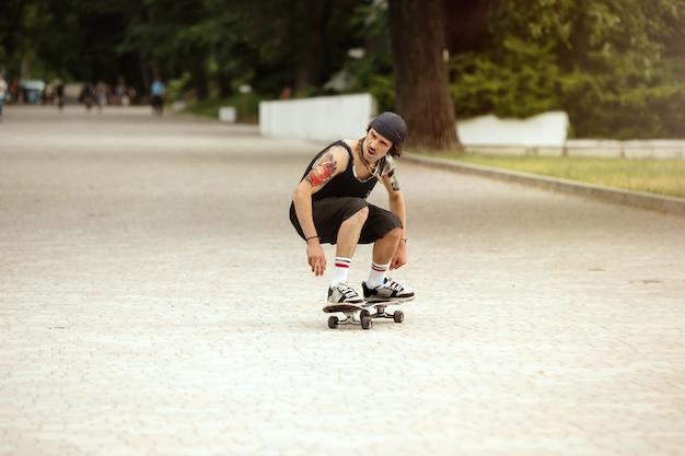 Guidatore di skateboard facendo un trucco per la strada della città in una giornata nuvolosa