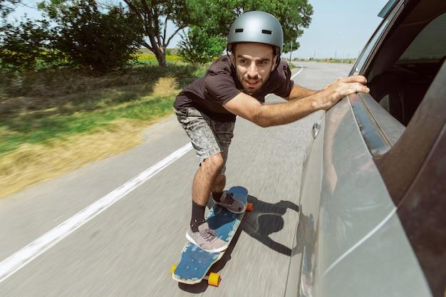 Guidatore di skateboard facendo un trucco sulla strada della città in una giornata di sole. giovane uomo in attrezzatura equitazione e longboard in azione. concetto di attività per il tempo libero, sport, estremo, hobby e movimento. veloce come una macchina.