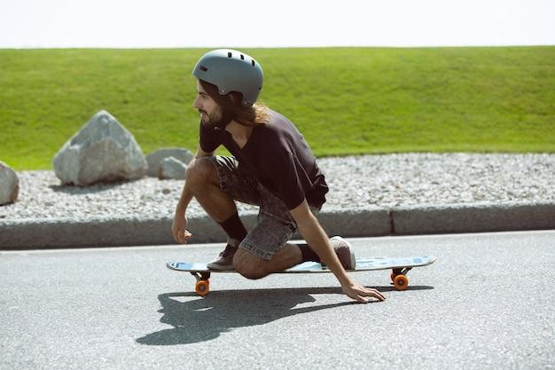 Guidatore di skateboard facendo un trucco sulla strada della città in una giornata di sole. giovane uomo in attrezzatura equitazione e longboard sull'asfalto in azione. concetto di attività per il tempo libero, sport, estremo, hobby e movimento.
