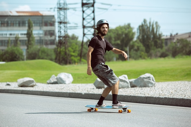 Skateboarder doing a trick at the city's street in sunny day. young man in equipment riding and longboarding on the asphalt in action. concept of leisure activity, sport, extreme, hobby and motion.