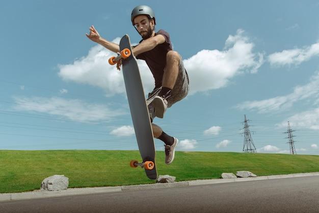 Guidatore di skateboard facendo un trucco sulla strada della città in una giornata di sole. giovane uomo in attrezzatura equitazione e longboard vicino a prato in azione. concetto di attività per il tempo libero, sport, estremo, hobby e movimento.