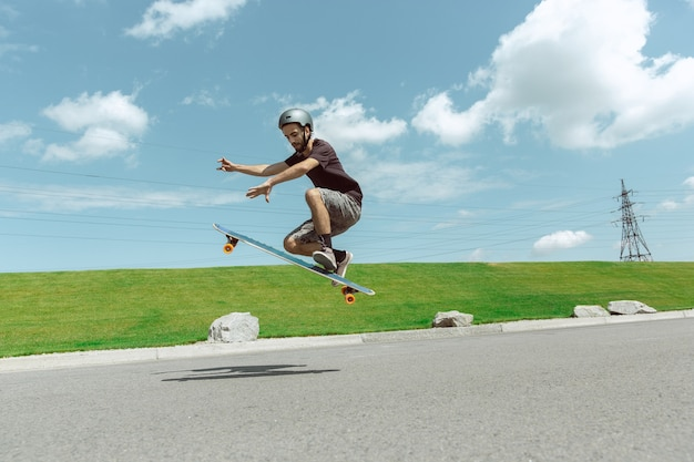 Skateboarder doing a trick at the city's street in sunny day. young man in equipment riding and longboarding near by meadow in action. concept of leisure activity, sport, extreme, hobby and motion.