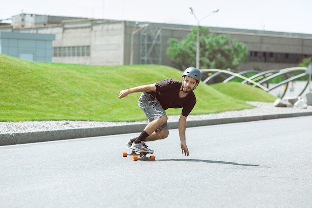 Skateboarder doing a trick at the city's street in sunny day