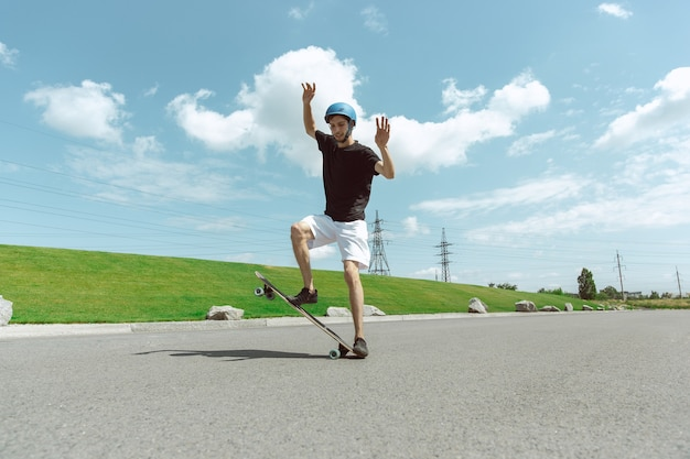 Skateboarder doing a trick at the city's street in sunny day.