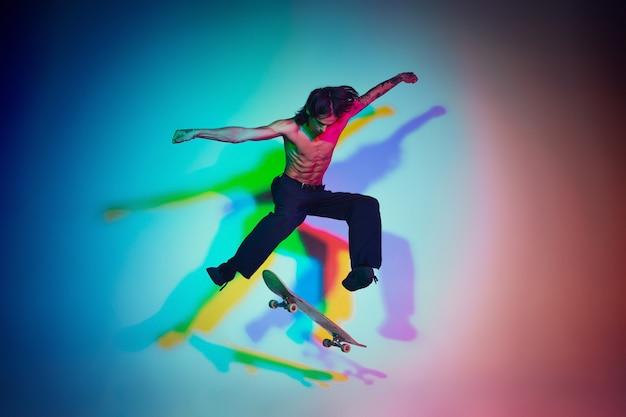 Skateboarder che fa un trucco isolato sullo studio