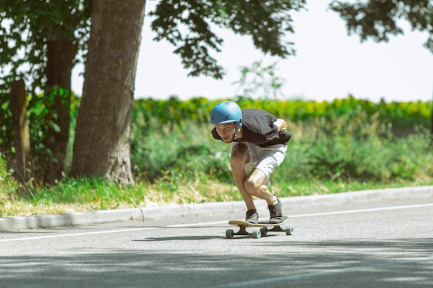 Skateboarder doing a trick near by meadow in sunny day. young man in equipment riding and longboarding on the asphalt in action. concept of leisure activity, sport, extreme, hobby and motion.