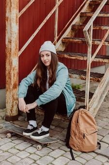 Ragazza di skateboarder e il suo skate in città