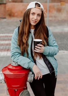 Ragazza dello skateboarder che tiene una tazza di caffè