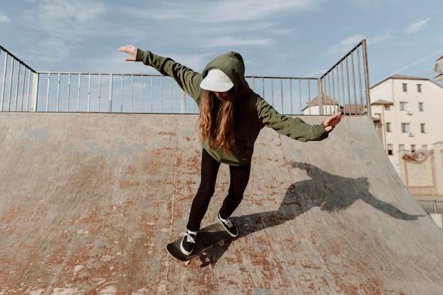 Ragazza di skateboarder sulla vista frontale della rampa