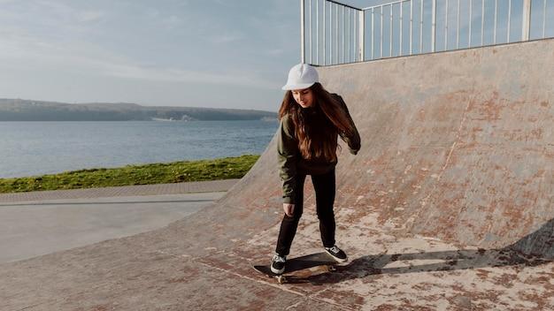 Ragazza di skateboarder sulla rampa campo lungo