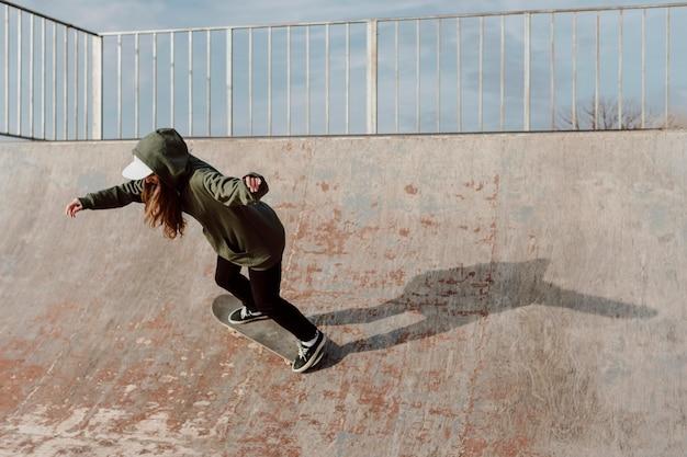 Ragazza skateboarder sulla rampa