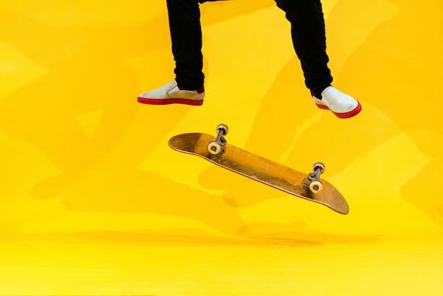 Скейтбордист выполняет трюк на скейтборде - кикфлип в студии. спортсмен практикует каскадерский прыжок на желтом фоне, готовясь к соревнованиям. экстремальный спорт, молодежная культура