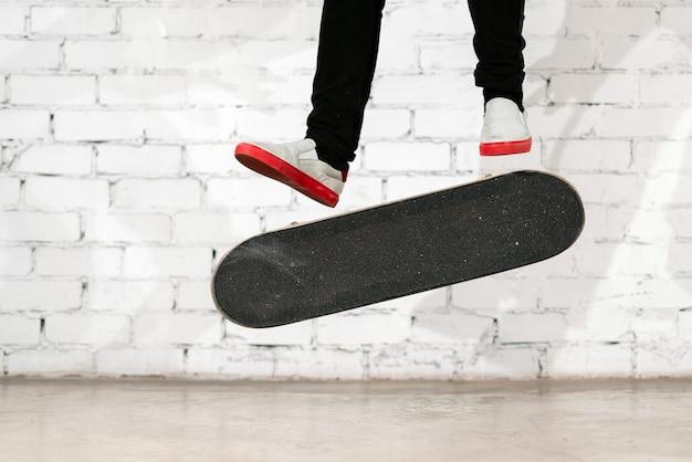 Скейтбордист выполняет трюк со скейтбордом - удар ногой по бетону.