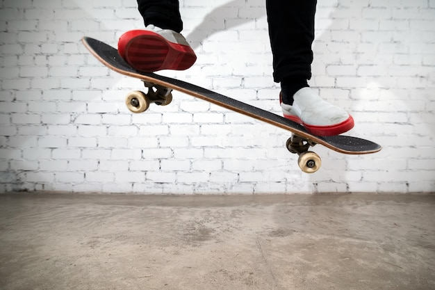 Скейтбордист выполняет трюк на скейтборде - олли на бетоне.
