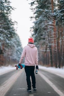 雪に囲まれた森の真ん中の道に立つスケートボーダー