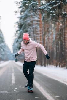 Guidatore di skateboard in piedi sulla strada in mezzo alla foresta circondata dalla neve