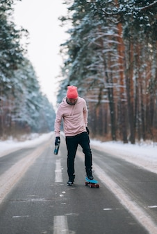 Skateboarder standing on the road in the middle of the forest surrounded by snow