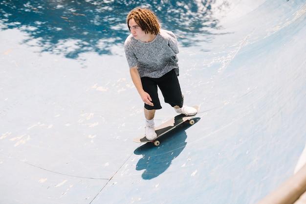 Skateboarder con dreadlocks praticare nel parco